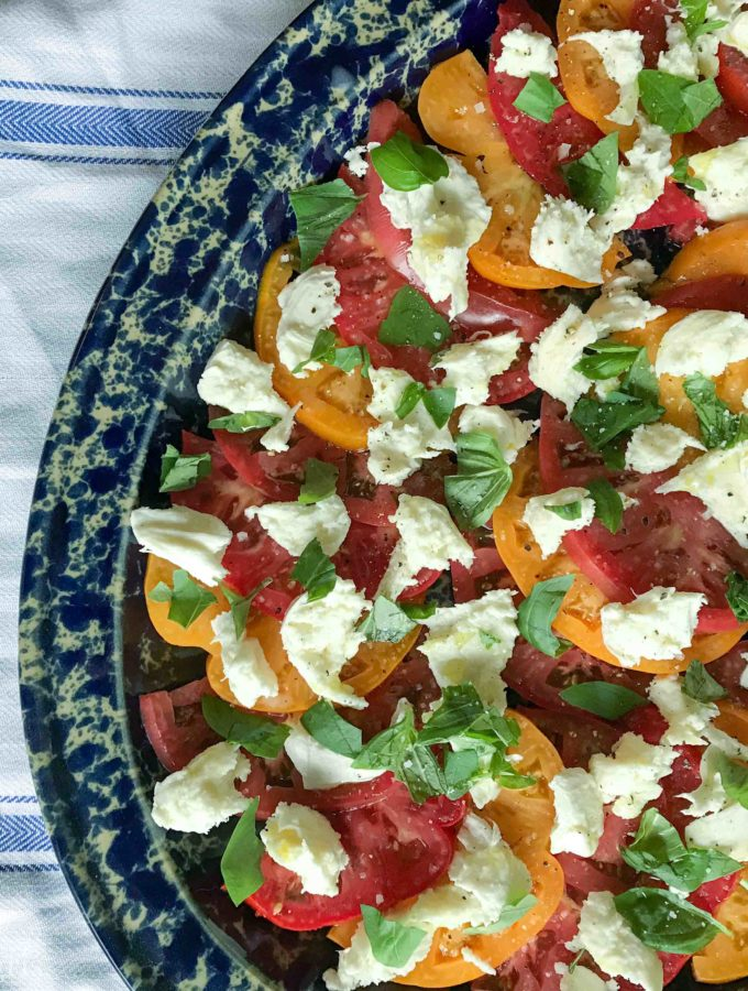 caprese on blue platter with cloth in background