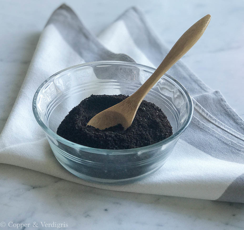 ground coffee in pyrex with wooden spoon