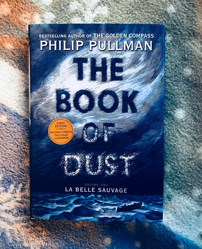 the book of dust by philip pullman on a blanket