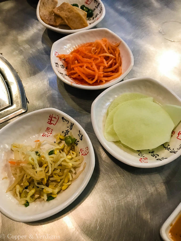 a series of four dishes with banchan